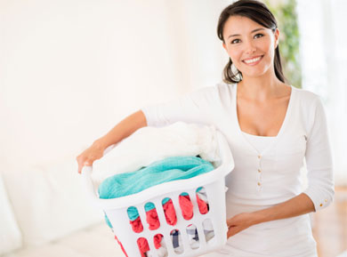 A lady with a basket of laundry under her arm